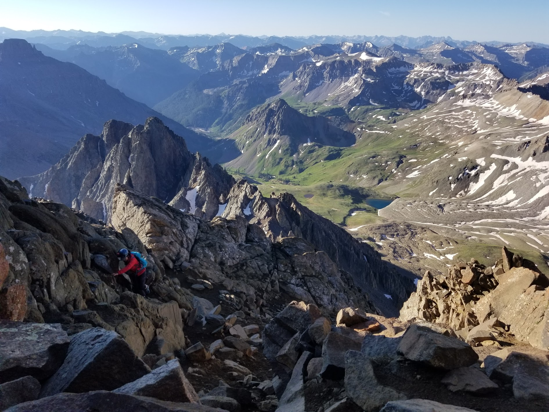 A climber in blue backpack is scrambling up a rocky path