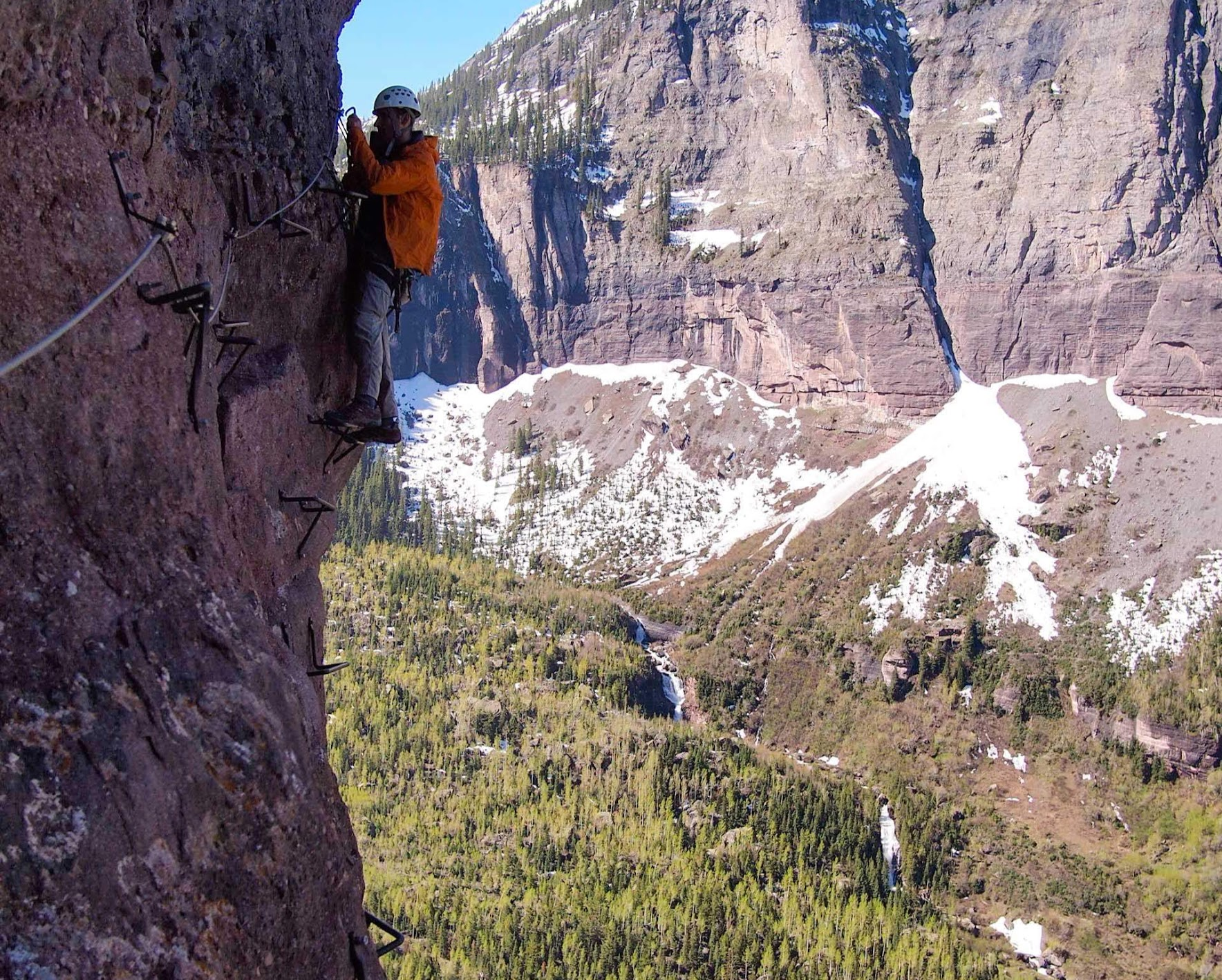 A climber in the middle of a via ferrata route above a tree-covered valley