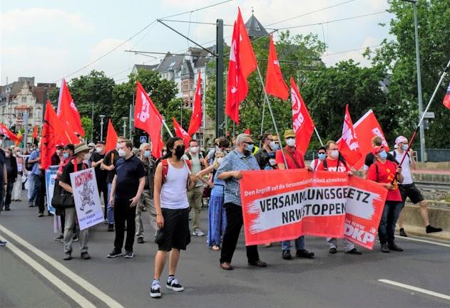 Demonstrierende mit DKP- und SDAJ-Fahnen, Transparent: «Versammlungsgesetz NRW stoppen, DKP».