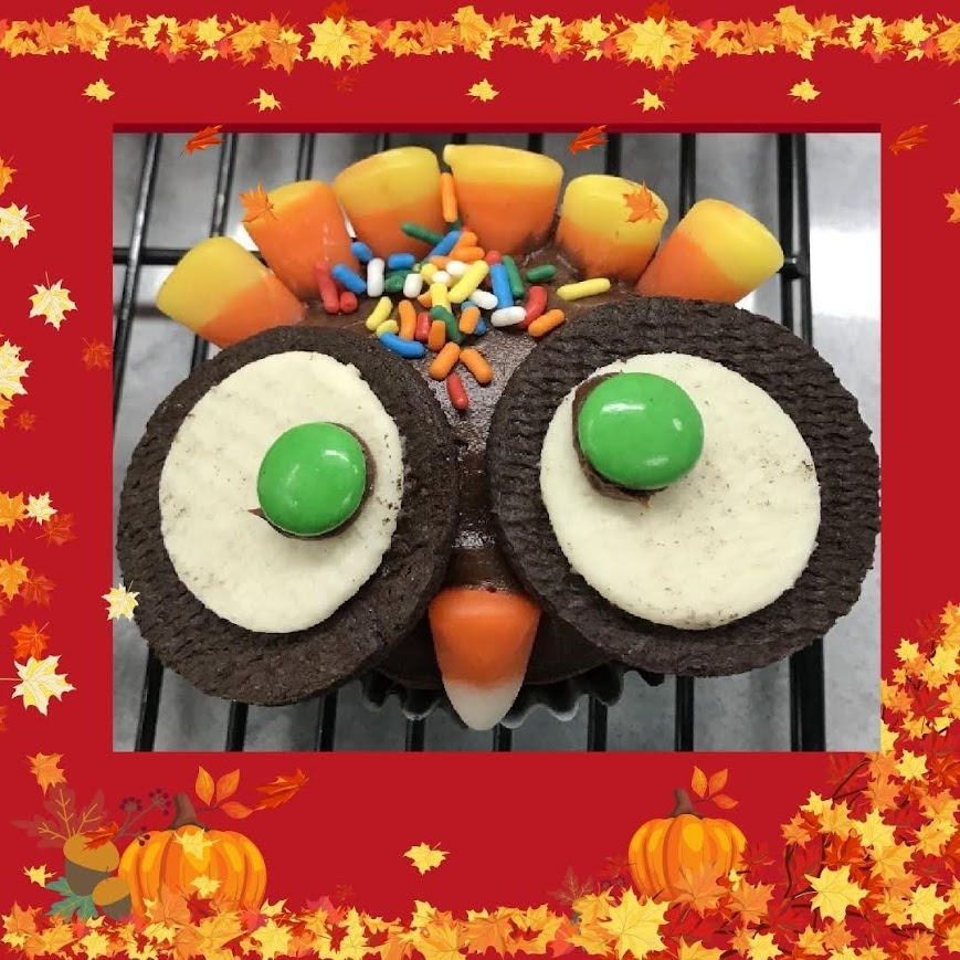 cupcake decorated like a turkey with sandwich cookie and candy eyes, candy corn feathers and beak and sprinkled face.