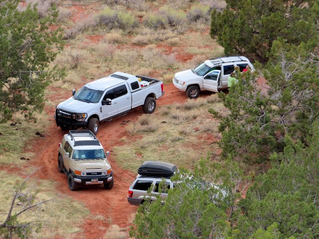 Vehicles parked below some rock art