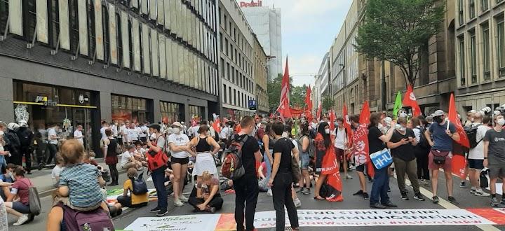 Demonstrierende mit Fahnen, einige sitzen auf der Straße.