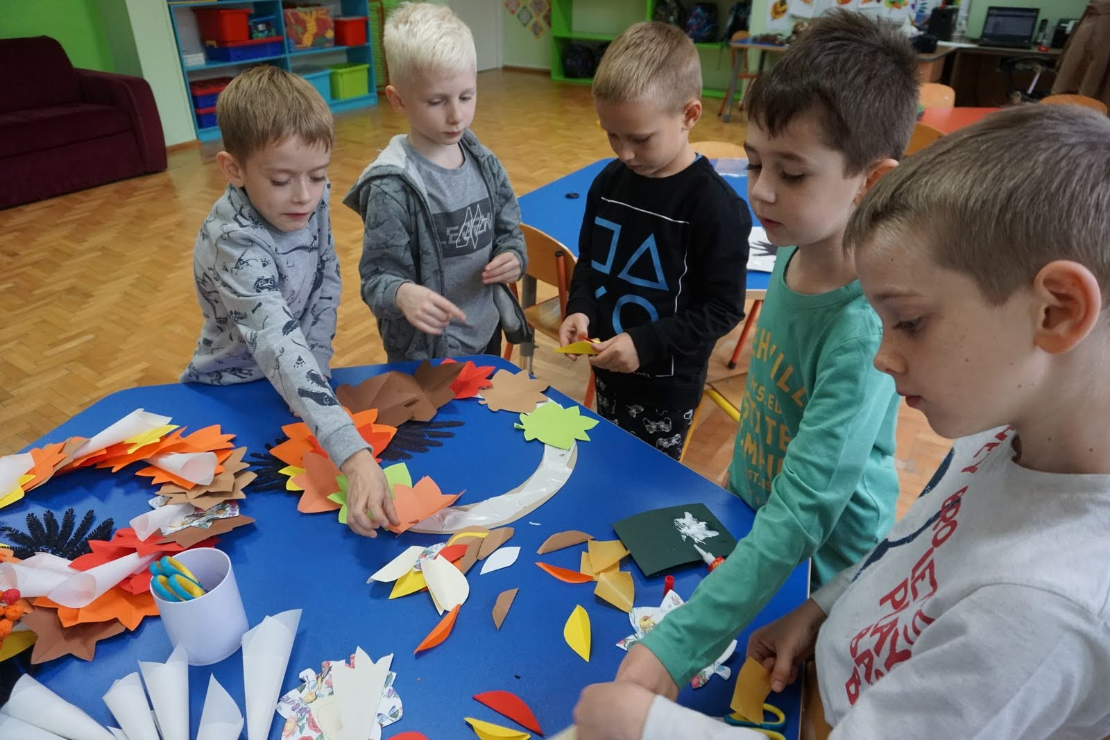 Uczniowie wykonują wieniec z liści