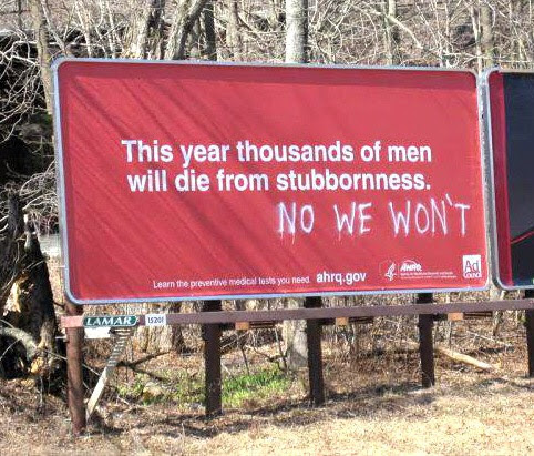 Red billboard with text, This year thousands of men will die from stubbornness. Spraypainted underneath, No we wont.