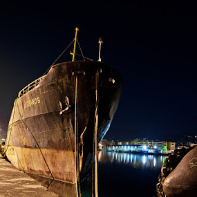Worn memories by Elias Spiliotis - Transportation Boats ( old, night photography, worn, ship, harbour, city lights, reflections, ropes,  )