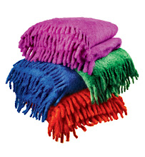 """Photo: HIJOS DE CECILIO VALGANON Exclusively ours. Mohair throws with fringe, shown in green, blue, orange, and purple. 51×59."""" $350. Also available in brown, ivory, silver, camel, turquoise, pink, and lavender. Spain. Seventh Floor. 212 872 2686"""