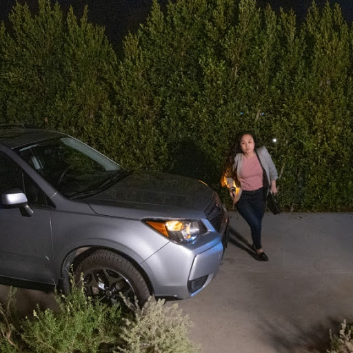 A person walks towards a house after getting out of their car in the driveway.
