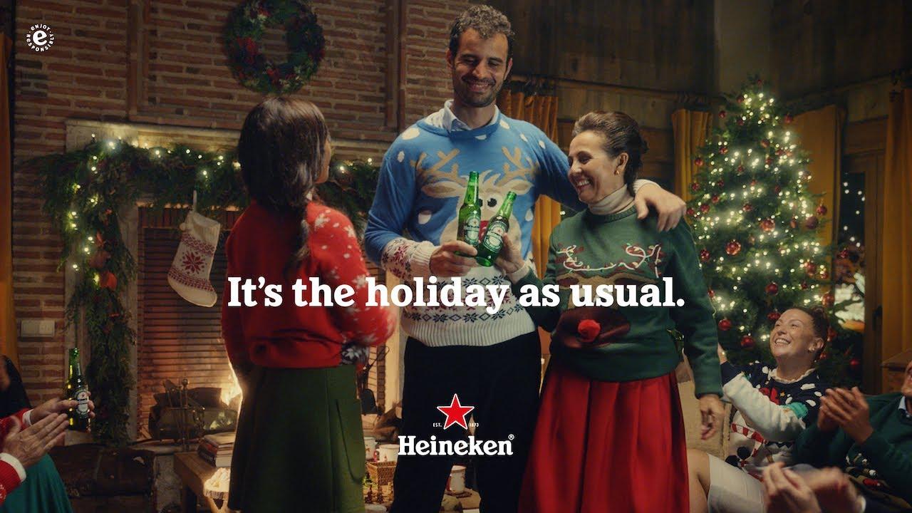 Fermo immagine della pubblicità birra Heineken che cita il claim it's the holiday as usual. Di sfondo, un ragazzo e la madre brindano con birre tra gli addobbi natalizi. Fonte: Marketing Ignorante