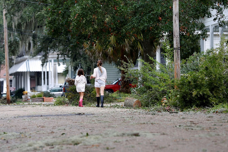 Residents walk down a street covered in debris scattered by Tropical Storm Nate, in Biloxi, Mississippi, the US, on Sunday. Picture:  REUTERS