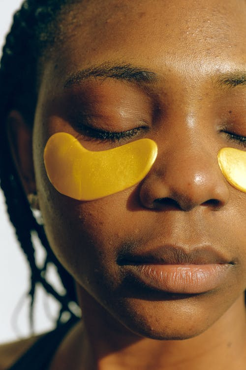 Crop gentle African American female with closed eyes and clean face enjoying cosmetic procedure for smoothing and moisturizing skin under eyes and removing dark circles