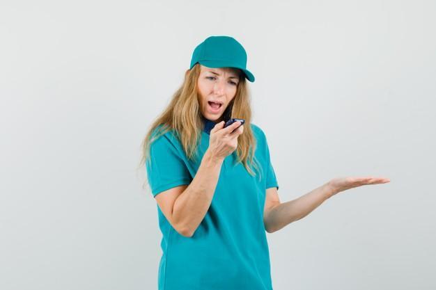 Entregadora de camiseta, boné falando no celular enquanto grita Foto gratuita