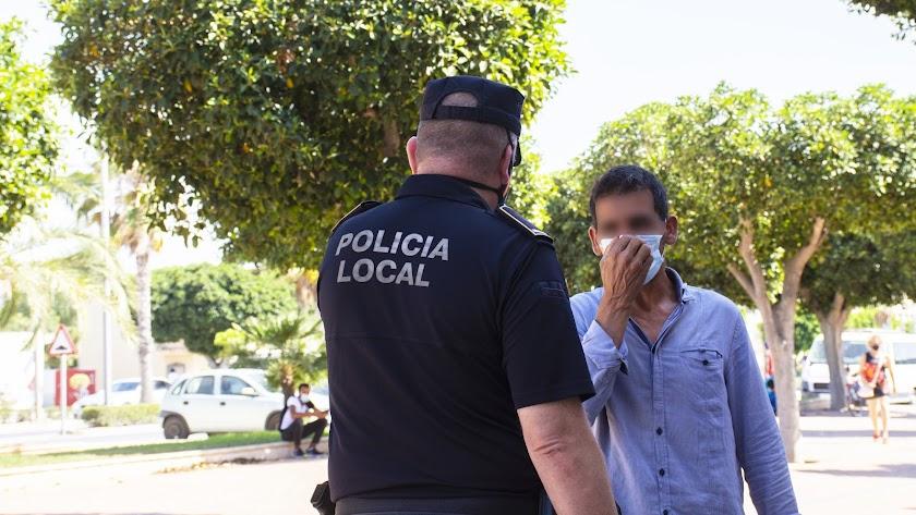 Un agente controlando el uso de la mascarilla.