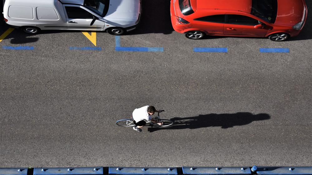 Foto de cima de ciclista e carros estacionados
