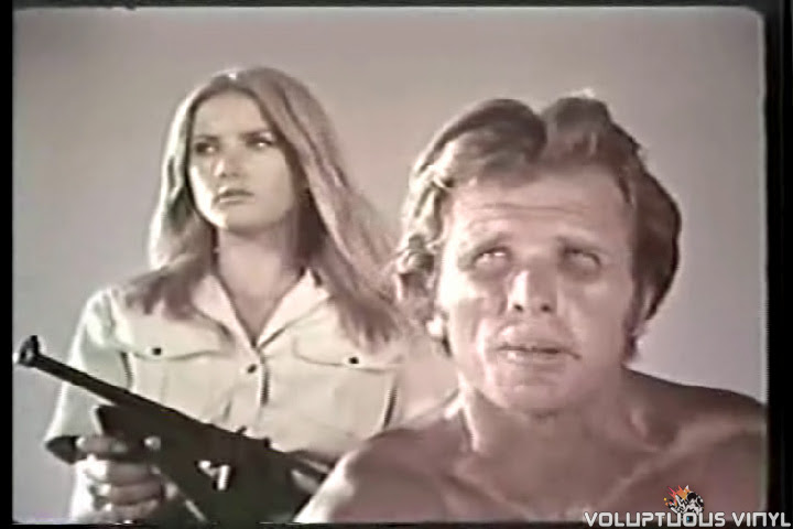Barbara Bouchet with a rifle behind Ron Ely in Tarzan