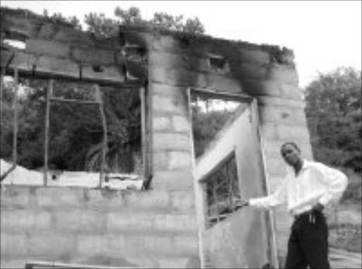FIRE TRAGEDY: Sowetan reporter Riot Hlatshwayo next to the burnt out shell of the house. Pic. Alfred Moselakgomo. © Sowetan.