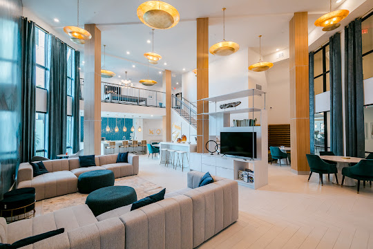 Upscale community clubhouse seating area with plush couches, TV, modern hanging light fixtures, and view of the kitchen and barstool area