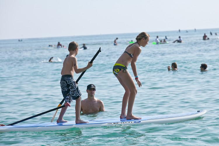 A couple of kids try longboarding along Waikiki Beach.