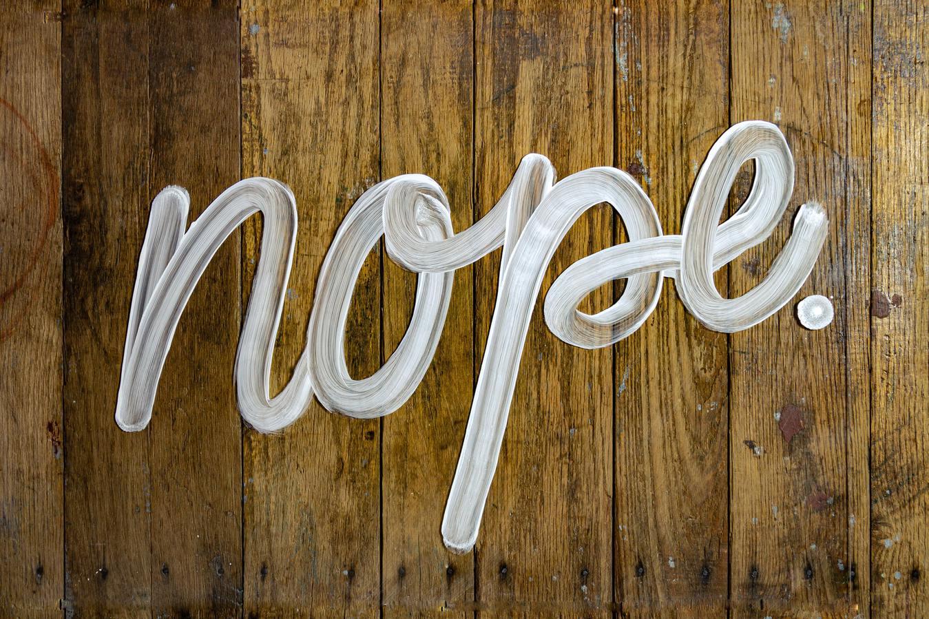 Nope napisane na drewnianym tle