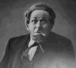 Photo: Henri Hesselinck (officieel Henri Louis van den Anker Hesselink), geb. Amsterdam 12-2-1869, overl. Gent 8-5-1947, vermoedelijk in de rol van Pancras Duif in Heijermans' Schakels. Op 8 februari 1945 vierde hij zijn 40-jarig jubileum als acteur in Gent. Gevoelsrollen in naturalistische stukken van Ibsen, Heijermans, Strindberg en Hauptmann lagen hem het beste. Hij was dan ook een meester in het weergeven van een fijngevoelige en bezielde tragiek. Als rasartist trad hij met veel sukses ook op in operettes en in werk van Vondel en Fabricius. Als regisseur bij een amateur toneelbond gold hij bij de spelers als een veeleisende brombeer. In 1928 werd hij benoemd tot Ridder in de Orde van Leopold II voor zijn verdiensten tot de verheffing van de toneelkunst in Vlaanderen. Het vak had hij geleerd van Louis Bouwmeester.   Zijn eerste vrouw was de bekende toneelspeelster Pauline Beersmans, dochter van de legendarische actrice Catharina Beersmans.  Hij hertrouwde met Madeleine de Laethouwer. Kinderen had hij niet.