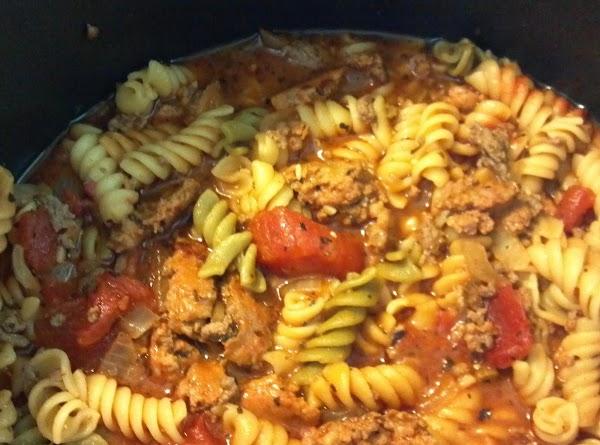 Stir in chicken broth, stewed tomatoes, tomato paste, rotini pasta,oregano, basil, salt & pepper. Bring...