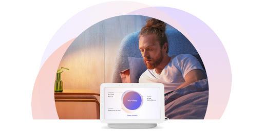 Mannen sitter upprätt i sängen och vänder sig mot sin Nest Hub-skärm bredvid sängen. Den visar anpassade underlag om sömnen.