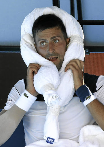 Hot competition: Novak Djokovic uses an iced towel in an attempt to cool down. At one point the court surface temperature was measured at 69°C. Picture: REUTERS