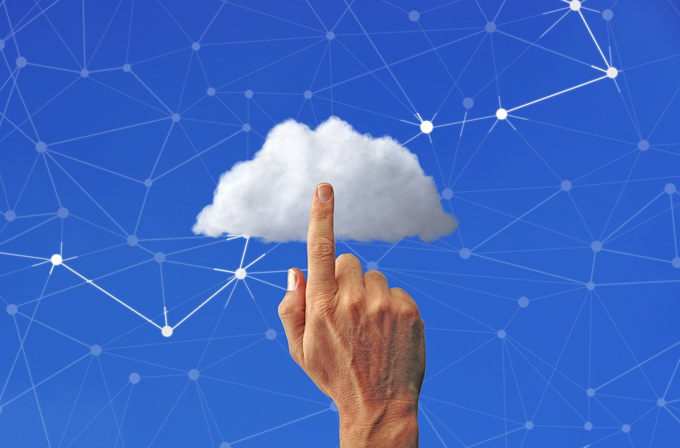 cloud computing benefits hand touching cloud with dotted lines and blue background
