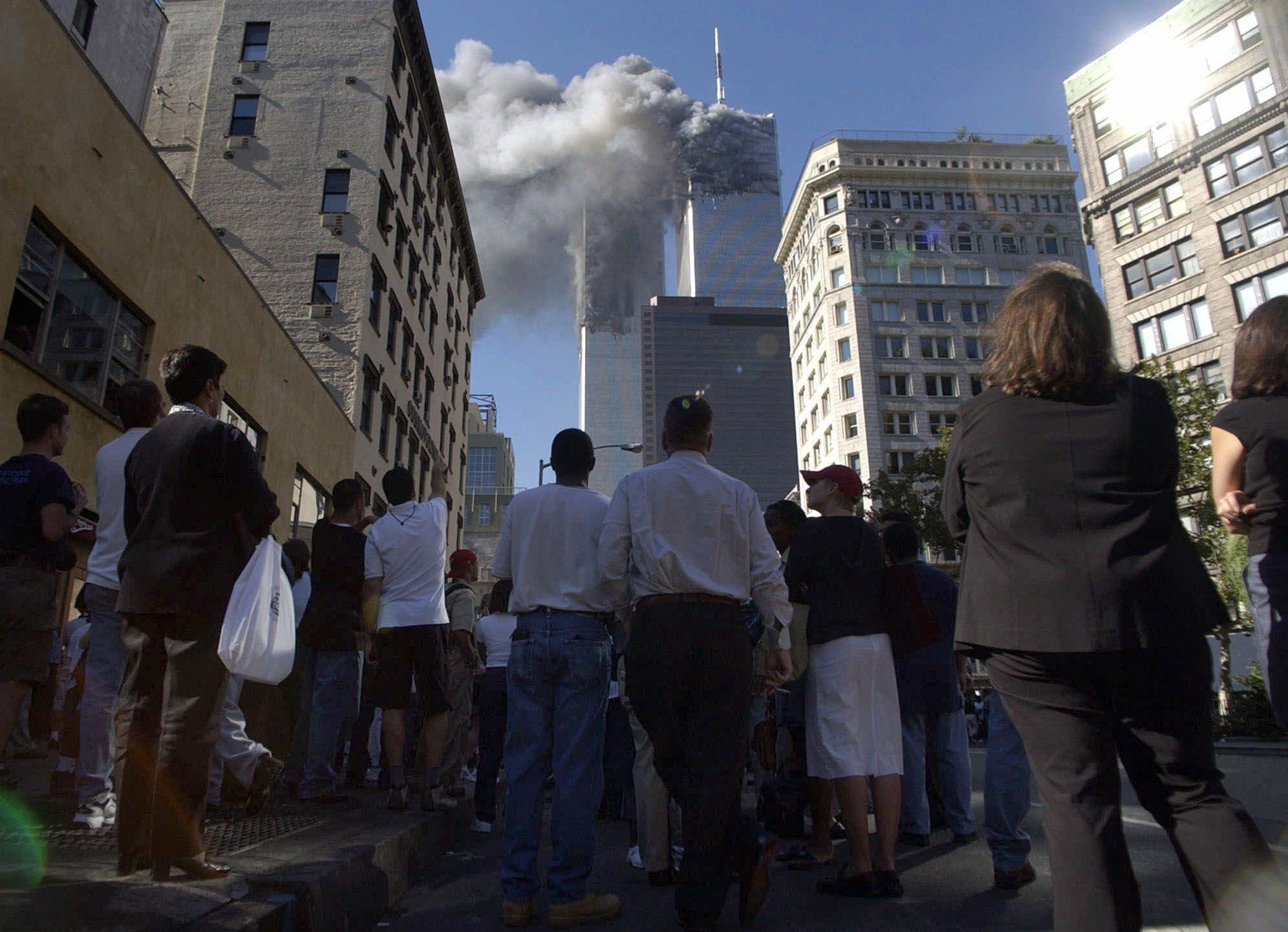 Pedestrians in lower Manhattan watch smoke billow from New York's World Trade Center on Tuesday, Sept. 11, 2001. (AP Photo/Amy Sancetta)