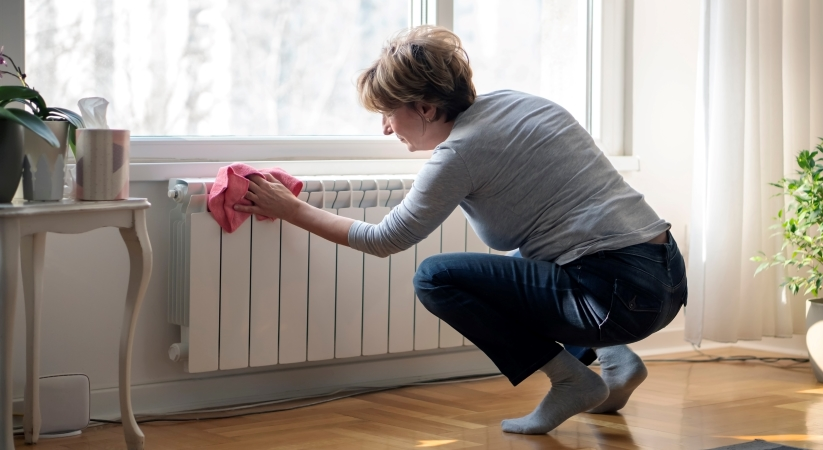 Woman cleaning a residential radiator.