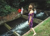vrouw kijkt toe hoe kinderen spelen bij een waterval
