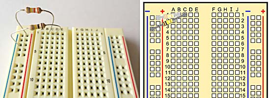 A breadboard with two resistors.