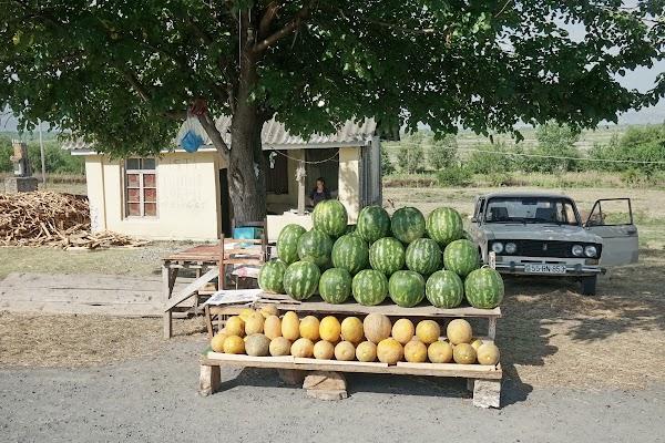 Neben der Straße bietet ein Händler Wassermelonen an.