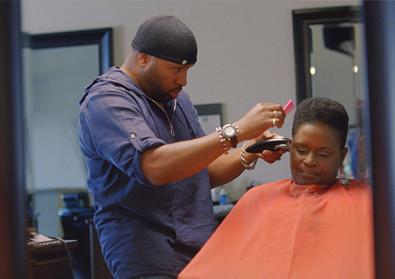 man cutting woman's hair in barber shop