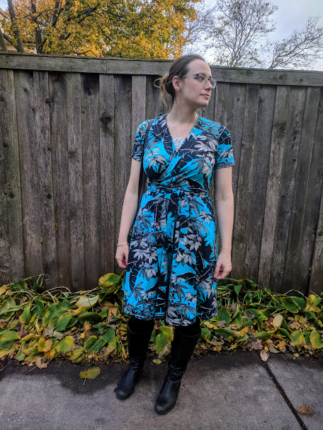Me, looking off to my left in a turquoise palm print Vogue 8379. I'm standing in front of a weathered wooden fence.