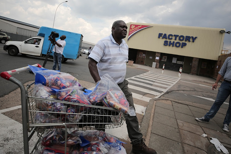 FILE PICTURE: Businessman Phillip Sibia queues to return meat from the Enterprise Factory store in Germiston, East of Johannesburg.