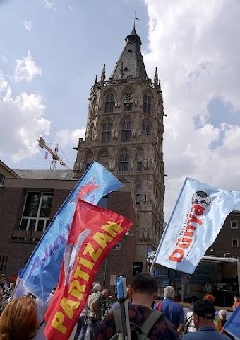 Demonstrierende mit Fahnen in Köln, im Hintergrund der Rathausturm.