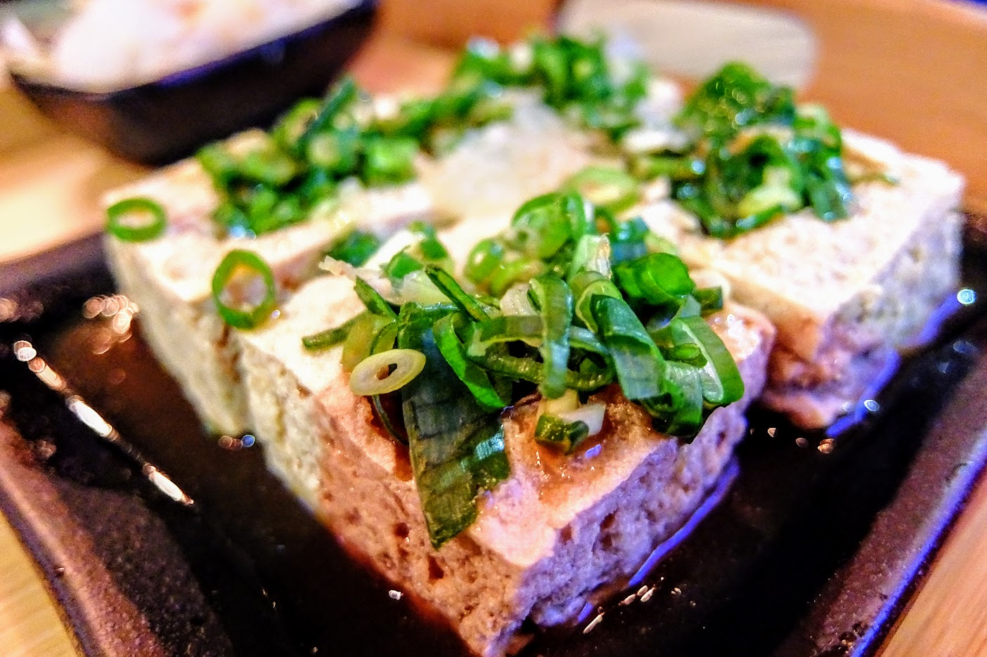 臭豆腐一份四塊,每一塊中間戳洞放入蔥花和蒜泥,底下則是醬油湯汁