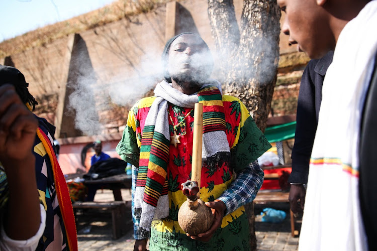 Members of the Rastafarian community smoke a marijuana pipe on, 18 September 2018, outside the Constitutional court in Johannesburg, after the court ruled that the private use of marijuana is not a criminal offence.