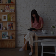 Woman sitting in breakfast nook, writing in journal