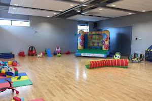 a kids play area setup in a room with wooden flooring with a jumping castle