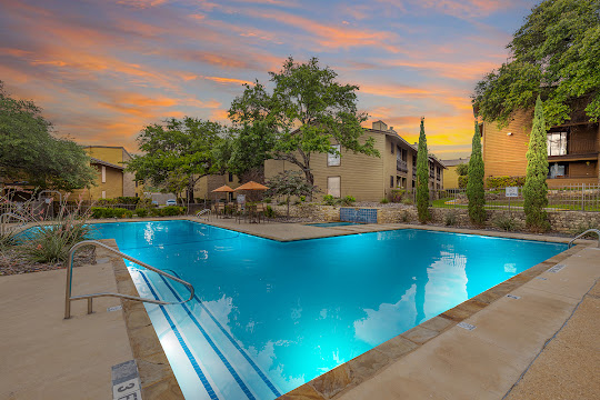 Tuscany Park's swimming pool and hot tub at dusk, surrounded by apartment buildings