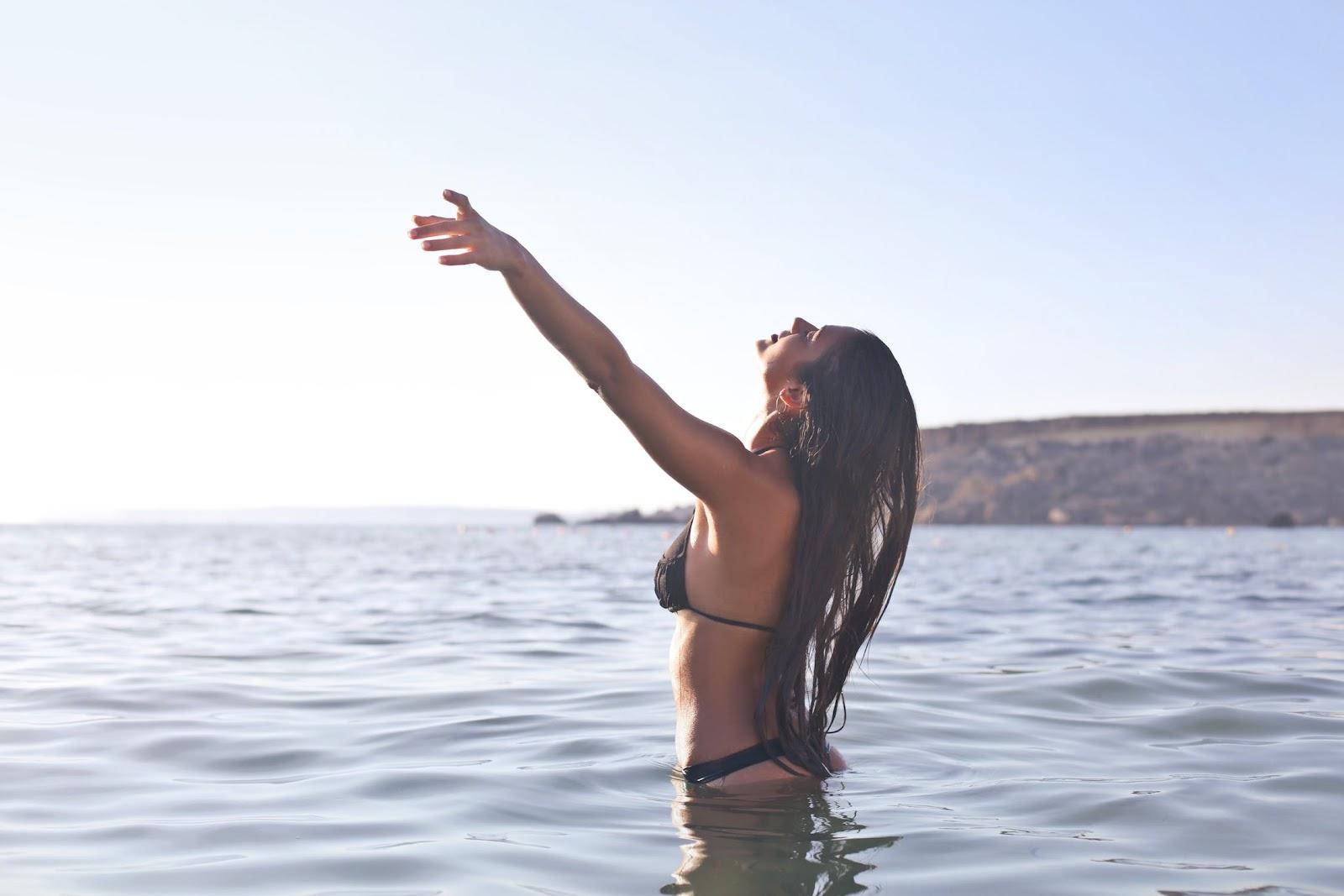 Mulher com braços levantados, olhos fechados em alto mar.