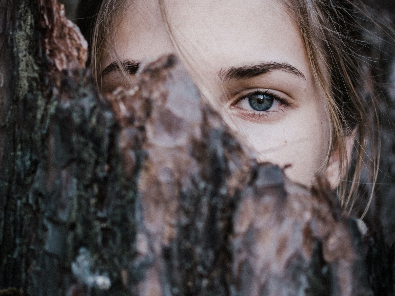 A white woman with her face half obscured by tree bark.