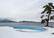 verlaten zwembad in de sneeuw naast een meer