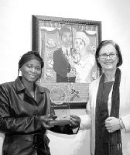 HER TIME: Lindiwe Xaba with Ann-Christin Wagenmann, the managing director of Beiersdorf, shows off her winning artwork, 'Izithandani'. © Sowetan.