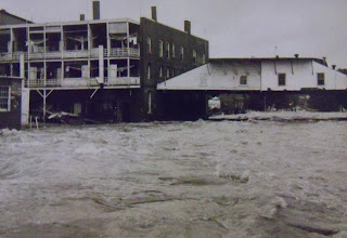 Photo: Water rushes under the roofs of what were once businesses on the Main Street bridge.