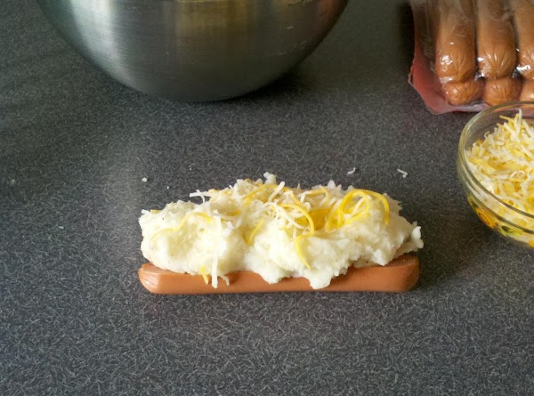 Cover the hot dog with the mashed potatoes and sprinkle with grated cheese and...