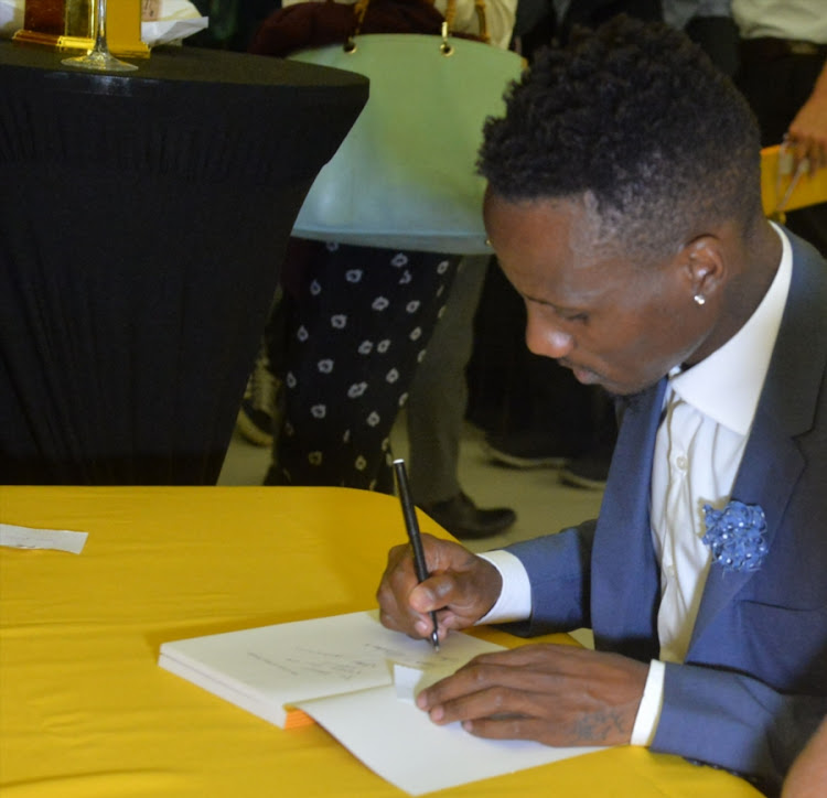 Teko Modise sign his book during the Launch of the book, The Curse of Teko Modise at Exclusive Books, Mall of Rosebank on November 29, 2017 in Johannesburg, South Africa.