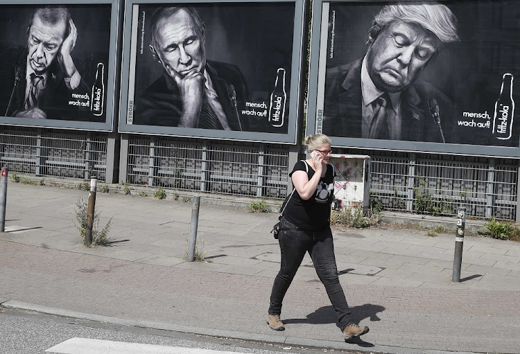 Leader board: A woman walks past advertising posters of a German soft-drink producer depicting Turkey's President Tayyip Erdogan, Russian President Vladimir Putin and US President Donald Trump during the G-20 summit in Hamburg. Picture: REUTERS