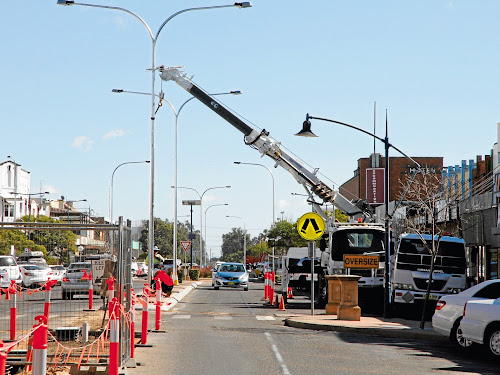 The 105 metre high lightpoles carrying two 150-watt high pressure sodium lamps cantilvered out over each carriageway are being progressively installed. the lights are speficially placed a certain distance apart to uniformly illuminate the street, and under the shop awnings which will allow future closed circuit television security cameras, with their cabling through the median strip, to 'see' what's going on at night.